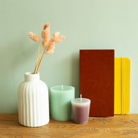 Notebook, candle, vase of dry flowers on wooden desk. green wall background. workspace