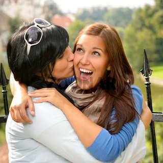 Mother kissing her daughter happy embrace outdoors