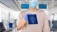 close up of woman holding immunity passport