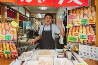 Friendly greeting vendor in his food stand selling fried japanese snack sticks, Miyajima, Japan