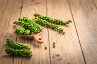 Fresh green peppercorns on wooden kitchen table.
