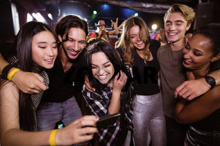 Cheerful friends looking at mobile phone while enjoying at nightclub