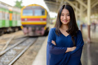 Happy young beautiful Asian tourist woman at the railway station