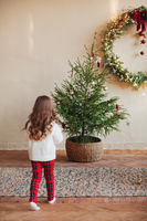 Cute little girl on carpet under by decorated christmas tree during winter holiday season