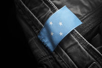 Tag on dark clothing in the form of the flag of the Federated States Micronesia