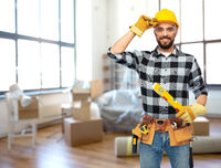 happy male builder in helmet with level at home