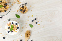 View of three bowls with muesli, nuts, blueberries and yoghurt on white wooden surface