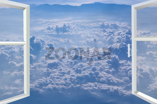 Window of room overlooking blue sky with white clouds. Heavenly landscape