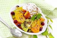 Salad fruit with cranberries in bowl on white wooden board