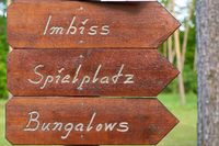 Signpost on a campsite in Germany with the inscription snack bar, playground, bungalows
