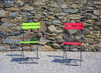 two folding chairs painted red and green before a stone wall