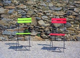 Zwei Klappstühle in rot und grün vor einer Steinwand