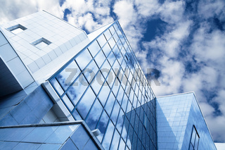 windows of skyscraper with reflections on a background cloudy sky