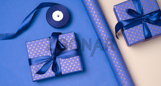 blue gift box wrapped in silk ribbon on a bluee background