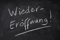 Wiedereroeffnung means reopening in German - handwritten text on chalkboard