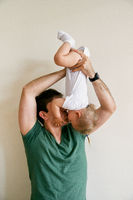 Smiling dad picks up little girl upside down and kiss her