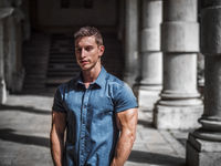 Handsome muscular blond man standing in city setting