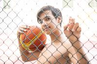 Teenage boy on city playground holding basketball ball