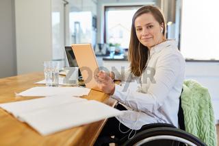Frau im Rollstuhl bei Videokonferenz im Wohnzimmer