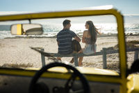 Happy caucasian couple next to beach buggy by the sea playing guitar