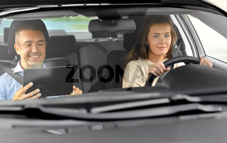 woman and driving school instructor talking in car