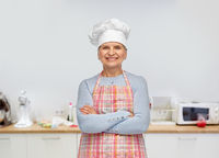 smiling senior woman or chef in toque in apron