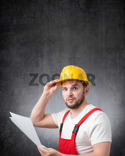 A confused construction worker holding papers or documents