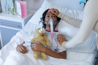 Mixed race mother in face mask touching sick daughter's head on oxygen ventilator in hospital