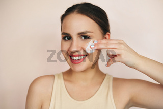 Young female smearing cream on face