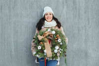 Brunette woman with Christmas wreath by the grey wall