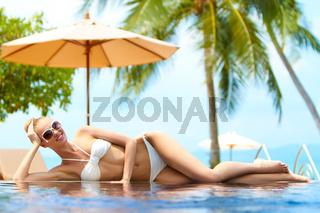 Sexy woman in a bikini on an infinity pool