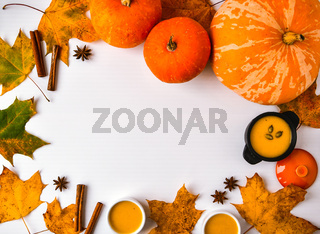Autumn food. Frame of pumpkin puree soup, leaves. Top view. Autumn harvest, pumpkins, leaves on grey as abstract background. Thanksgiving day. Flat lay. Copy space