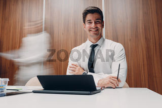 Businessman using laptop sit at table in office meeting background with walking people with motion blur. Business people man and woman group conference discussion