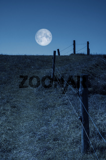 moon over a hill and a fence