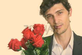 Close up of young handsome businessman holding red roses