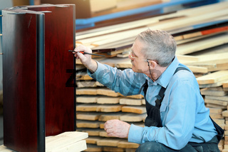 An elderly man with glasses and gray hair works with wood in a carpentry shop.