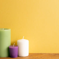Color candles on wooden table. yellow wall background. home interior