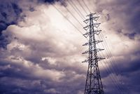 High power electrical pole on a cloudy day with silhouette