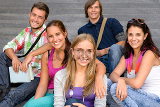 Students sitting on school stairs smiling teens