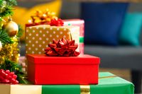 Composition of christmas tree and stack of presents on blurred background