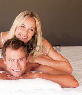 Young couple having fun together lying on bed