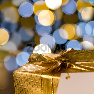 Christmas gift with label sparkling lights background