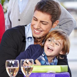 Lachendes Kind feiert Geburtstag mit Vater