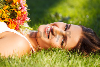 Beautiful young girl relaxing on green grass