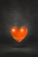 3D orange heart on a black studio background
