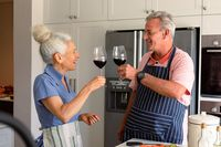 Happy caucasian senior couple standing in kitchen, drinking wine and preparing meal together