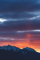 Alpine mountains with snow tops at sunset with dramatic stormy cloudscape in Tirol, Austria