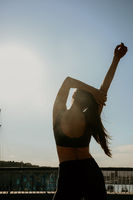 Back view of sporty young woman doing stretching outdoor.