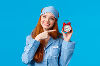 Dont forget wake up on time. Cheerful and cute relaxed feminine redhead woman in pyjama and sleep mask, holding red clock, pointing at alarm as set up before sleep, standing blue background