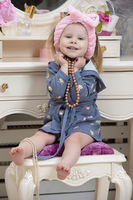 A cute little girl is sitting at the dressing table and holding beads.